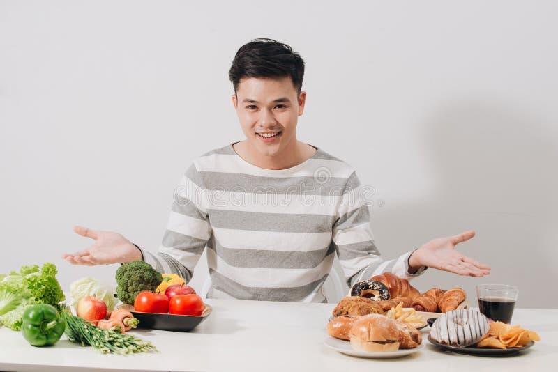 Homem que tem a escolha dura entre o alimento saudável e insalubre imagens de stock royalty free