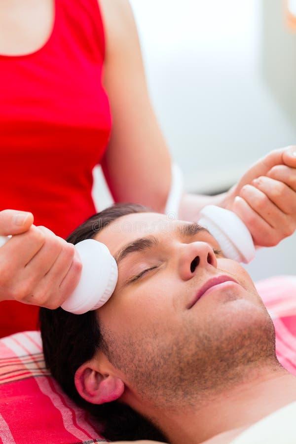 Homem que tem a massagem de cara em termas do bem-estar fotografia de stock royalty free