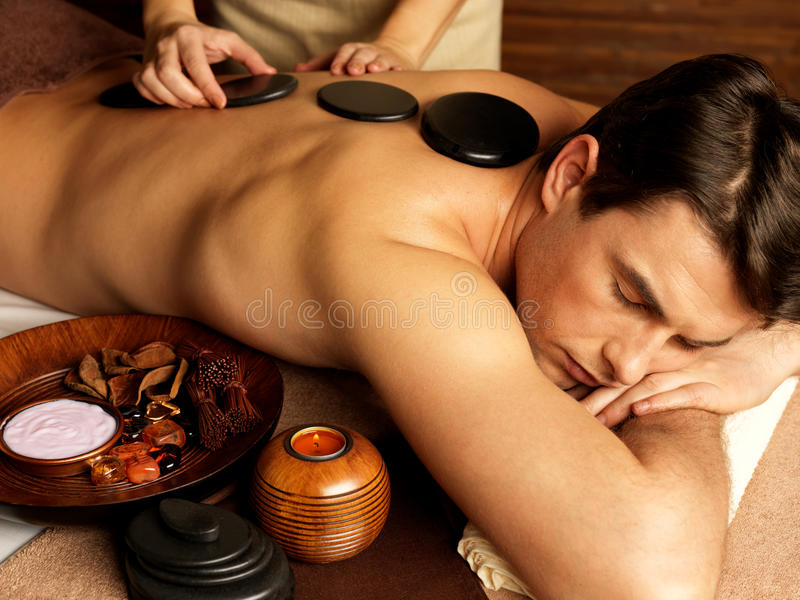 Homem que tem a massagem de pedra no salão de beleza dos termas fotos de stock