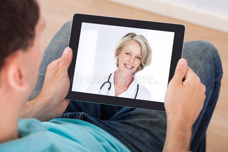 Homem que tem o bate-papo video com doutor fêmea imagem de stock royalty free