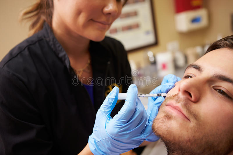 Homem que tem o tratamento de Botox na clínica da beleza imagens de stock royalty free