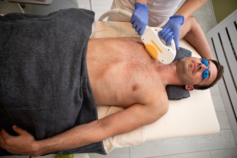 Homem que tem o tratamento do laser na cl?nica da beleza imagens de stock royalty free