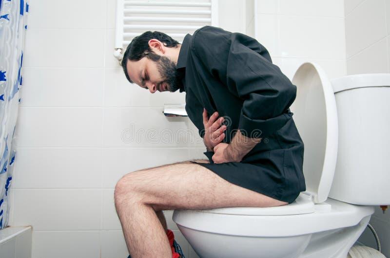 Homem que tem problemas no toalete imagens de stock