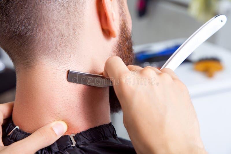 Homem que tem uma barbeação na barbearia imagem de stock royalty free