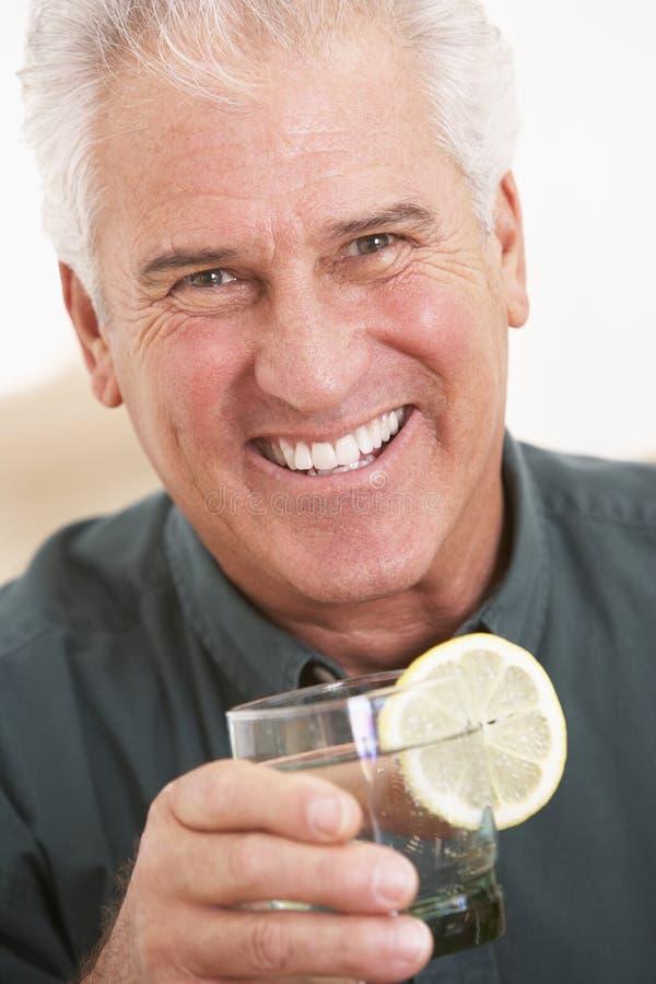 Homem que tem uma bebida em casa fotos de stock royalty free