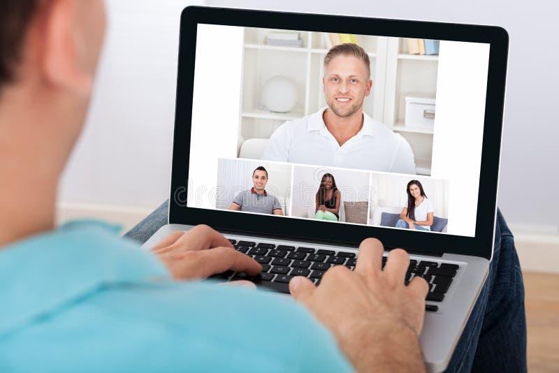 Homem que tem a videoconferência com amigos imagens de stock