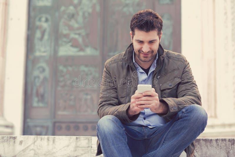 Homem que texting no telefone Indivíduo urbano ocasional que usa a construção velha de sorriso da cidade da parte externa feliz d fotos de stock