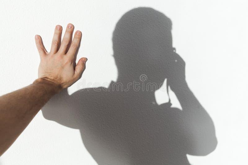 Homem que toca em sua sombra na parede branca imagem de stock royalty free