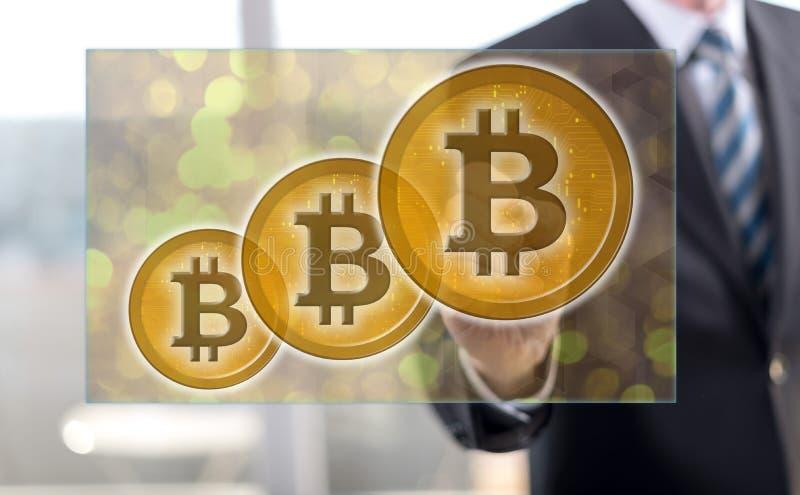 Homem que toca em um conceito da moeda do bitcoin fotografia de stock royalty free