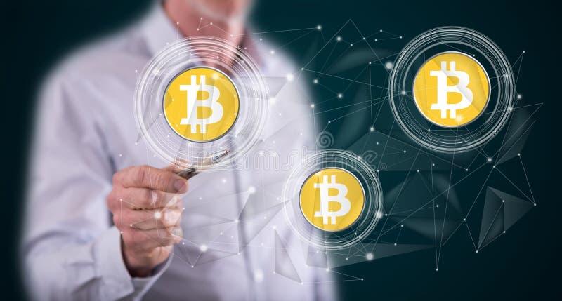 Homem que toca no conceito da moeda do bitcoin foto de stock