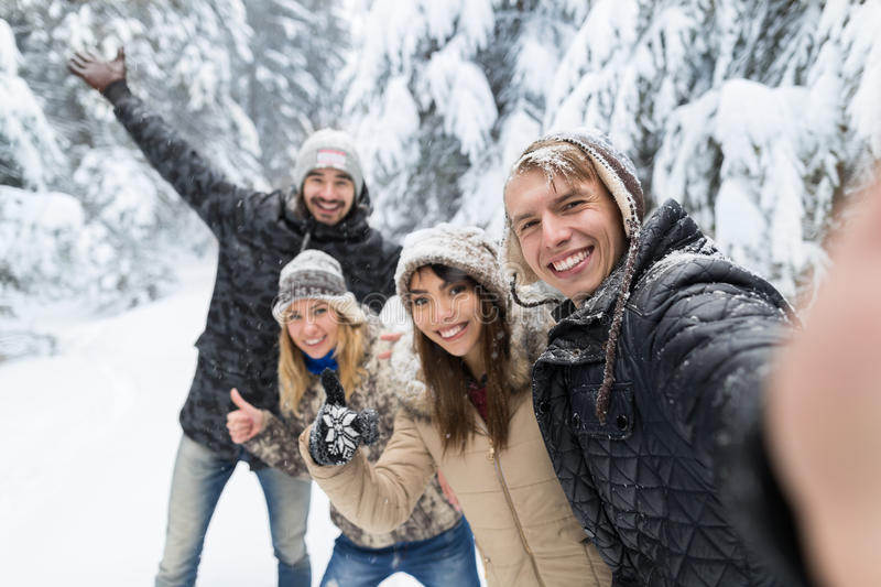 Homem que toma a amigos da foto de Selfie a neve Forest Young People Group Outdoor do sorriso fotos de stock royalty free