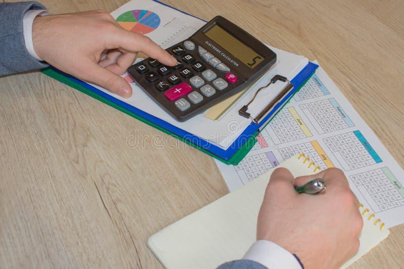 Homem que toma as notas, calculadora na tabela Motivação do sucesso, riqueza dos fluxos financeiros fotos de stock