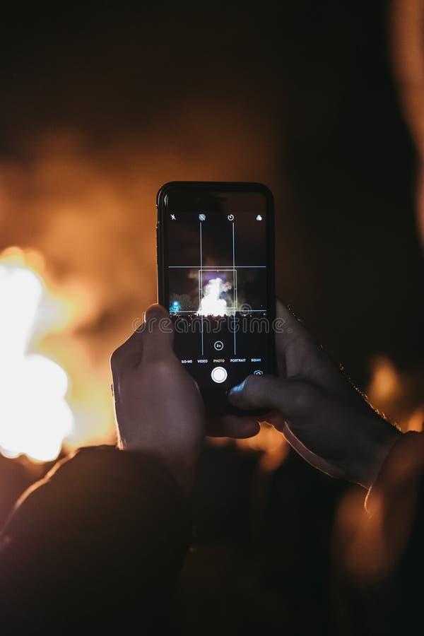 Homem que toma a foto da fogueira no telefone celular em Guy Fawkes Night fotografia de stock