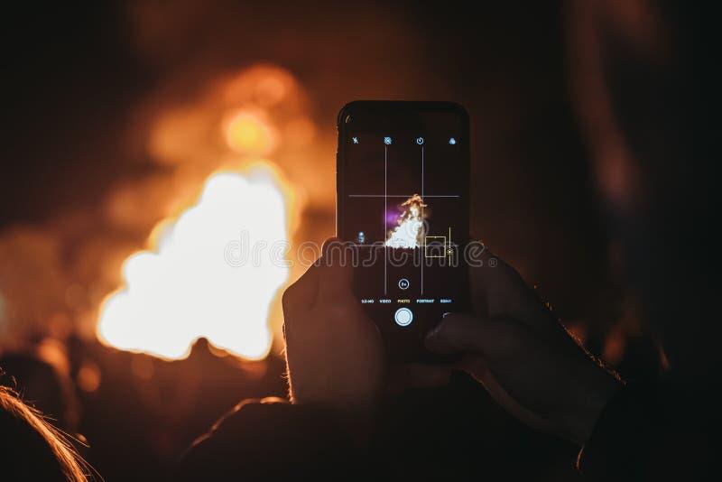 Homem que toma a foto da fogueira no telefone celular em Guy Fawkes Night imagem de stock