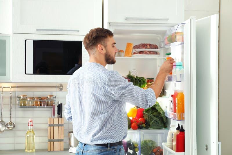 Homem que toma a garrafa com suco fora do refrigerador fotografia de stock
