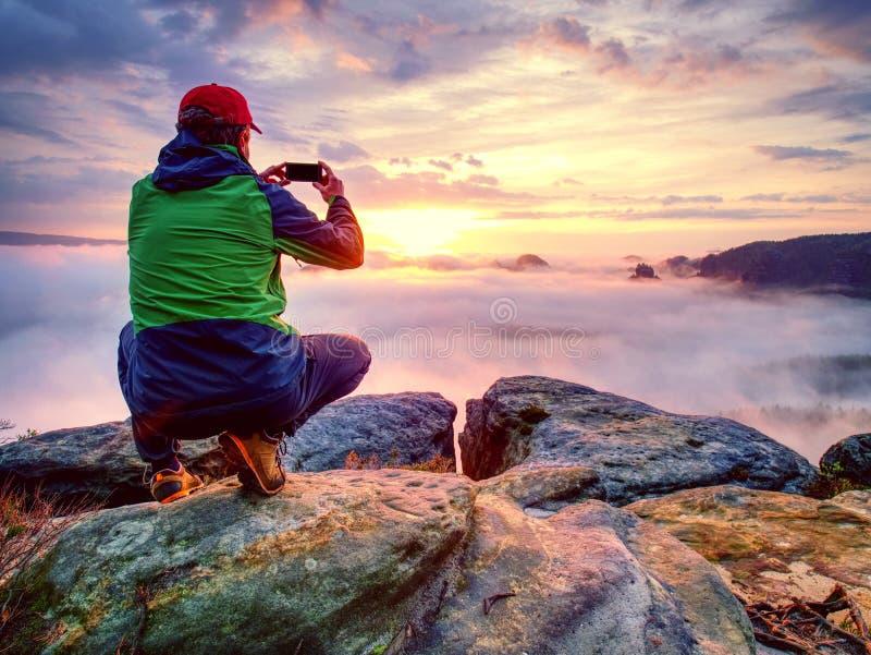 Homem que toma a imagem de montanhas de surpresa da queda em seu telefone foto de stock