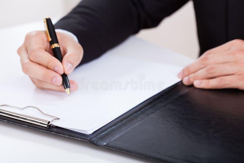 Homem que toma notas em uma reunião imagem de stock royalty free
