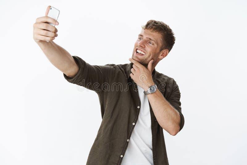 Homem que toma o selfie para afixar em linha por favor seguidores, smartphone deleitado e 'sexy', tocante do sorriso do queixo da imagem de stock