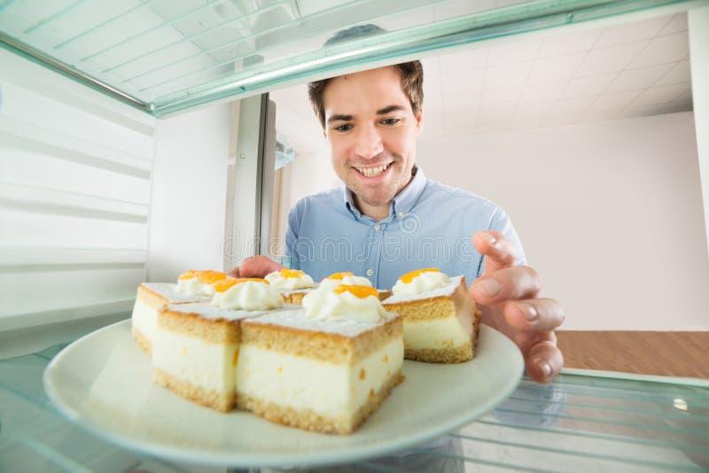 Homem que toma a opinião do bolo do interior do refrigerador imagens de stock royalty free