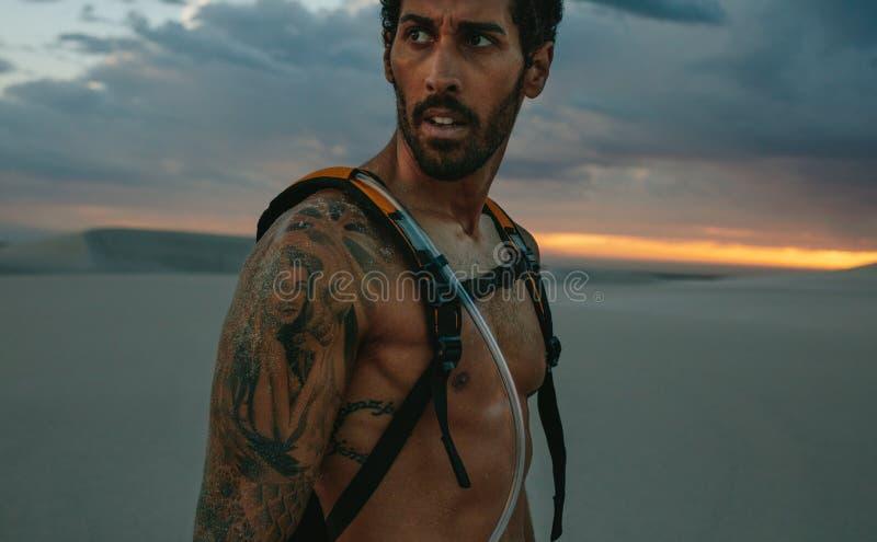 Homem que toma a ruptura do exercício no deserto fotos de stock royalty free