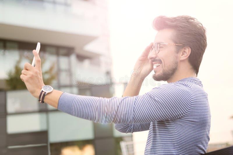 Homem que toma um selfie com um smartphone imagem de stock royalty free