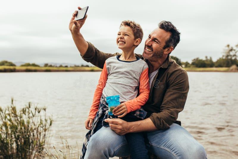 Homem que toma um selfie usando um telefone celular fotos de stock royalty free