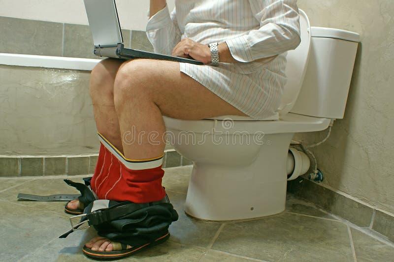 Homem que trabalha com seu portátil no WC fotos de stock royalty free