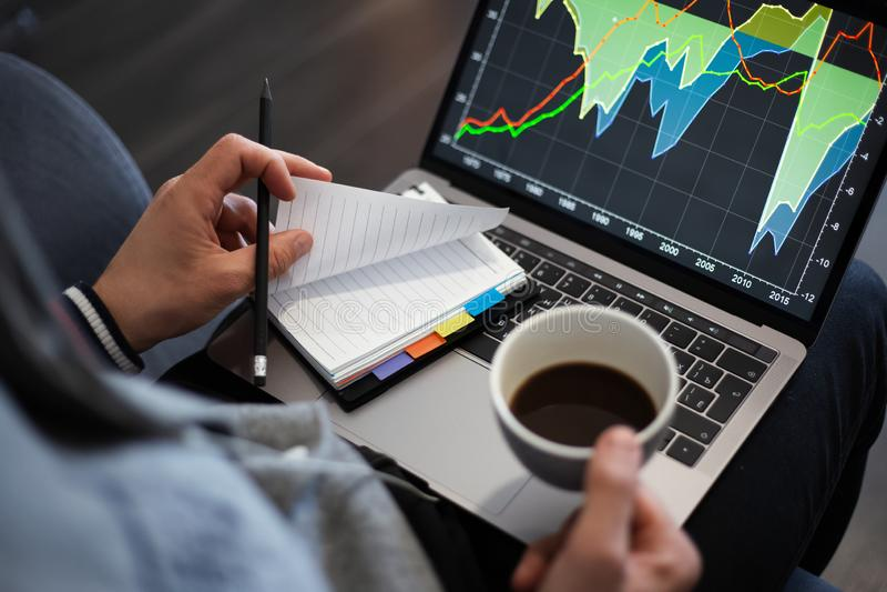 Homem que trabalha em um projeto no portátil com uma xícara de café imagem de stock royalty free