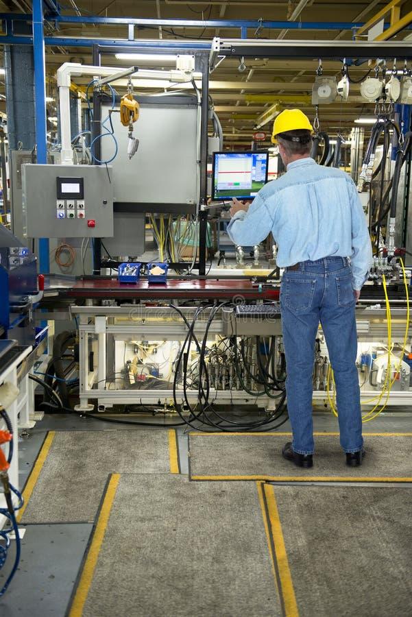 Homem que trabalha na fábrica industrial da fabricação fotografia de stock