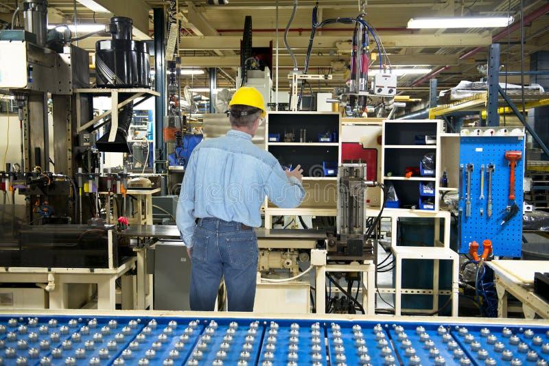Homem que trabalha na fábrica industrial da fabricação foto de stock