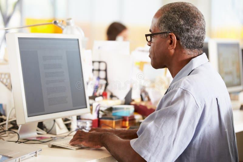 Homem que trabalha na mesa no escritório criativo ocupado fotos de stock
