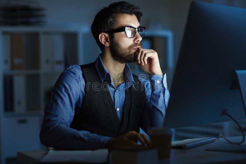 Homem que trabalha na noite fotografia de stock royalty free