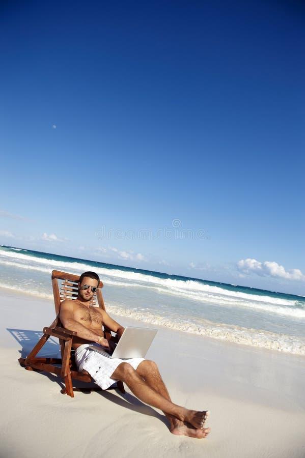 Homem que trabalha na praia imagens de stock