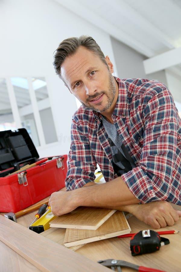 Homem que trabalha nas pranchas de madeira DIY em casa imagem de stock