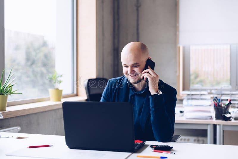 Homem que trabalha no escritório no laptop foto de stock