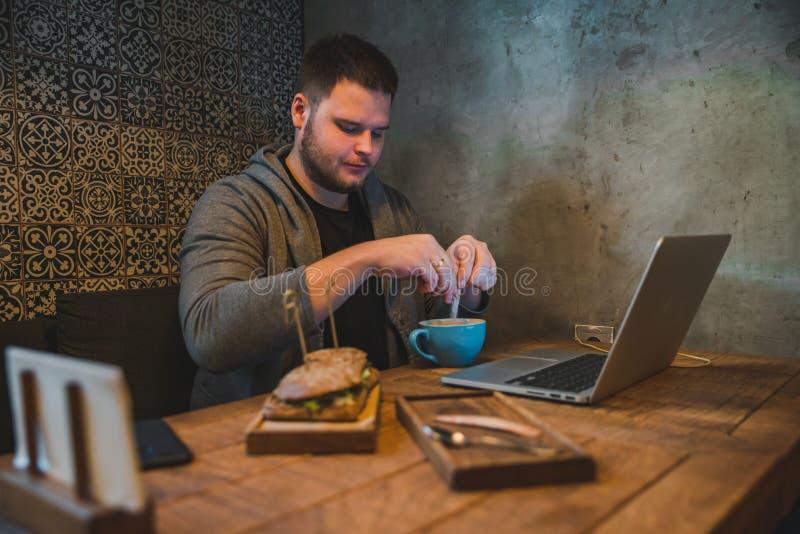 Homem que trabalha no portátil no café sanduíche e café do café da manhã imagens de stock