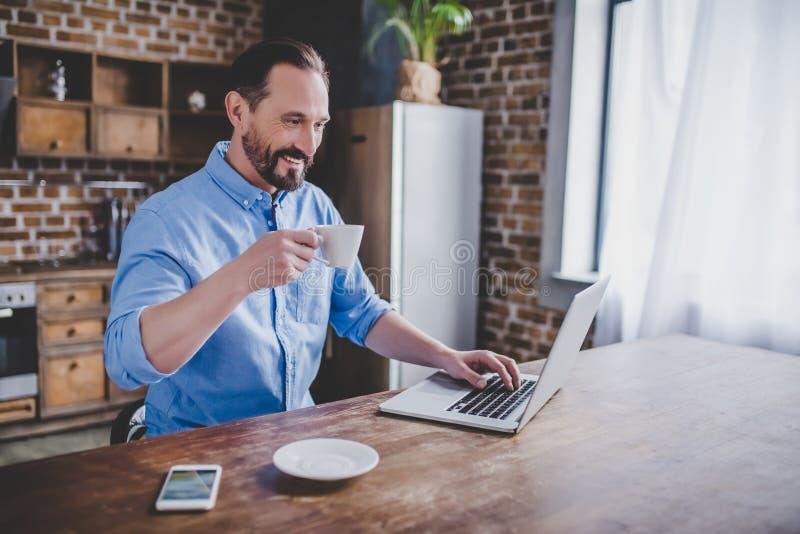 Homem que trabalha no portátil na cozinha fotografia de stock royalty free