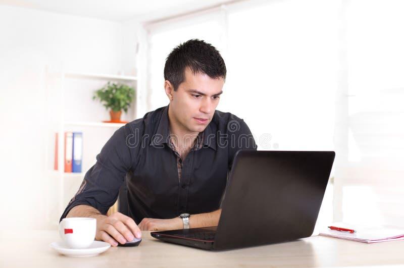 Homem que trabalha no portátil no escritório fotografia de stock