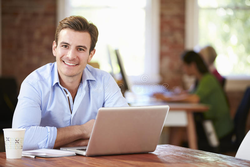 Homem que trabalha no portátil no escritório contemporâneo foto de stock royalty free