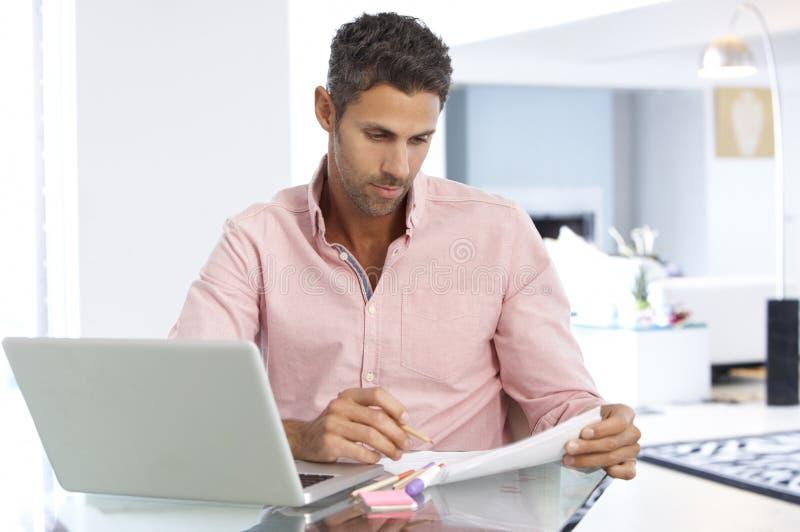 Homem que trabalha no portátil no escritório domiciliário fotos de stock royalty free