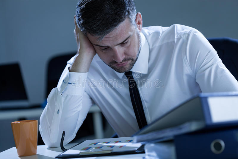 Homem que trabalha tarde no escritório fotografia de stock royalty free