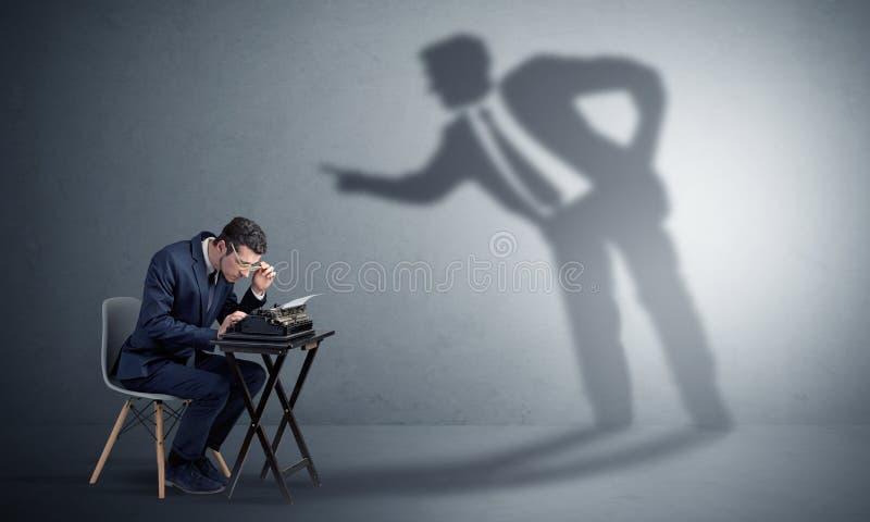 Homem que trabalham duramente e sombra que discute com ele foto de stock royalty free