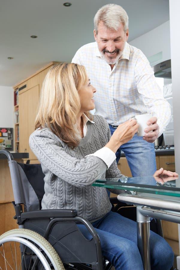 Homem que traz a mulher na bebida quente da cadeira de rodas em casa fotos de stock royalty free