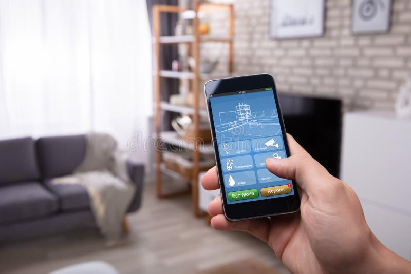 Homem que usa a aplica??o do Smart Home no telefone celular foto de stock royalty free