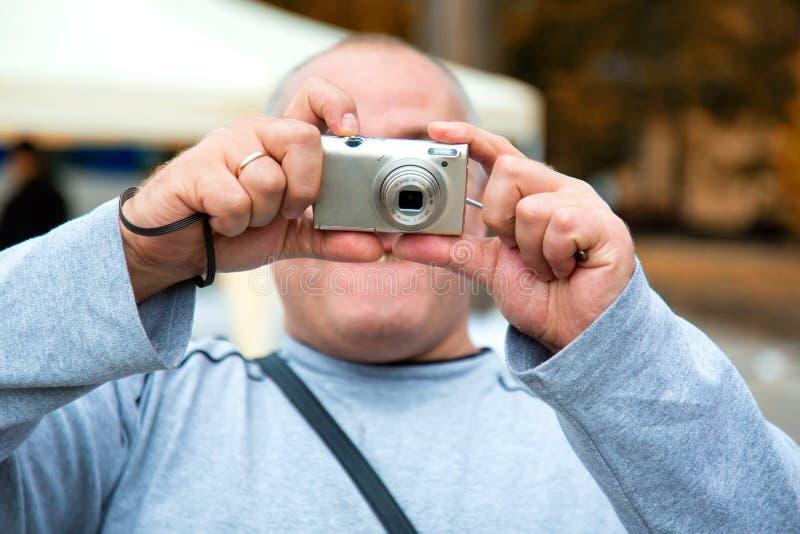 Homem que usa a câmera compacta foto de stock