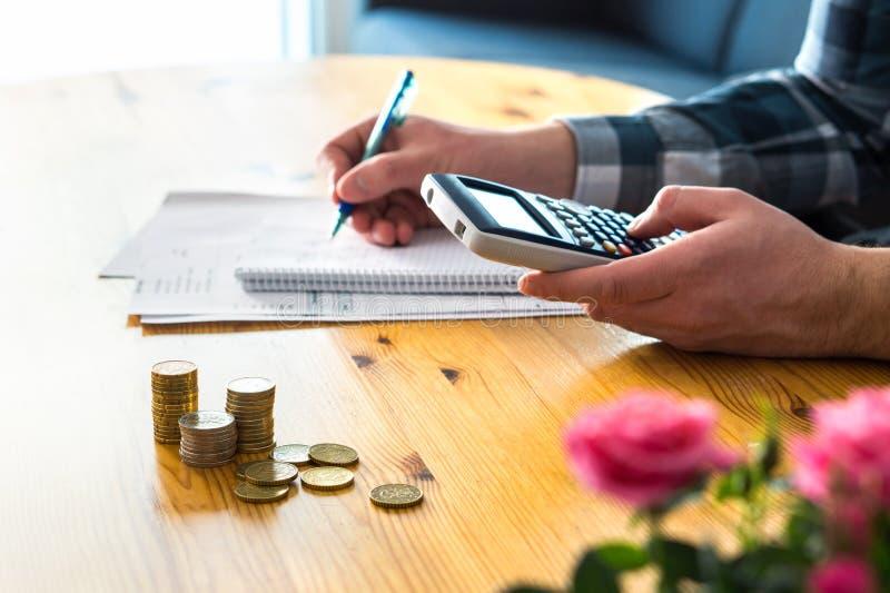 Homem que usa a calculadora e contando o orçamento, as despesas e as economias