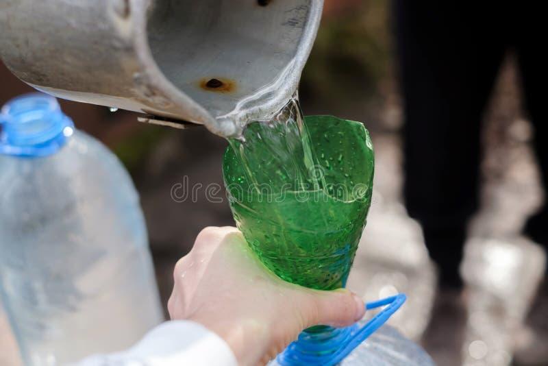 Homem que usa a colher e a água do desenho do funil de bem fotografia de stock