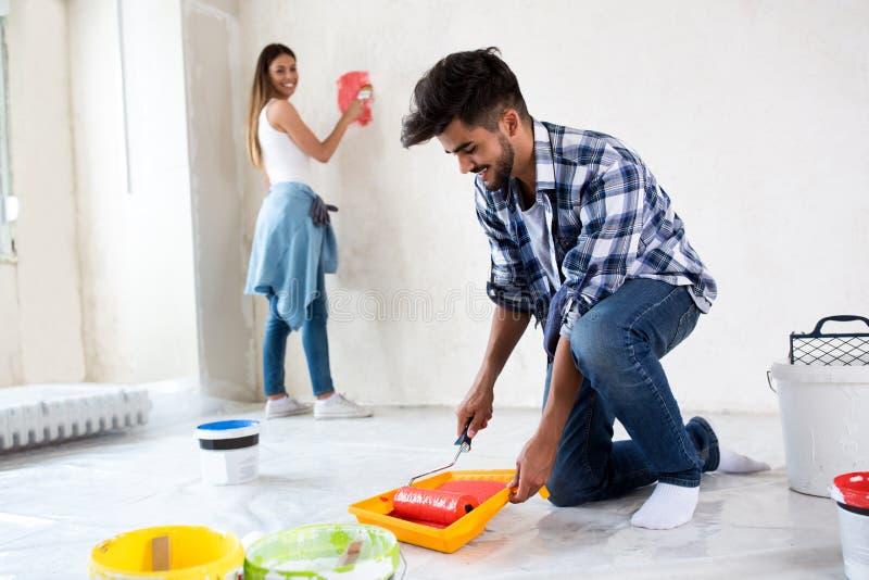 Homem que usa a cor da tomada com o rolo à casa de pintura imagens de stock royalty free