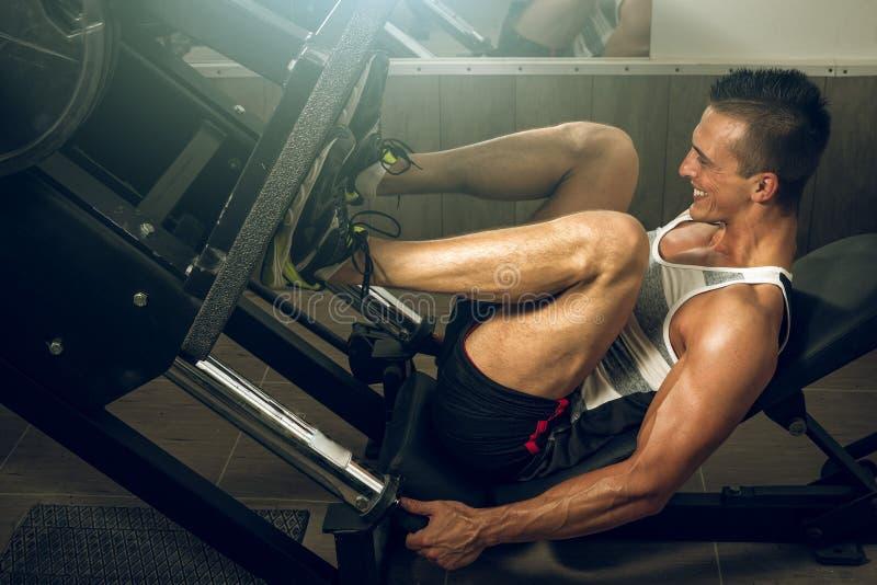 Homem que usa a imprensa do pé no gym foto de stock