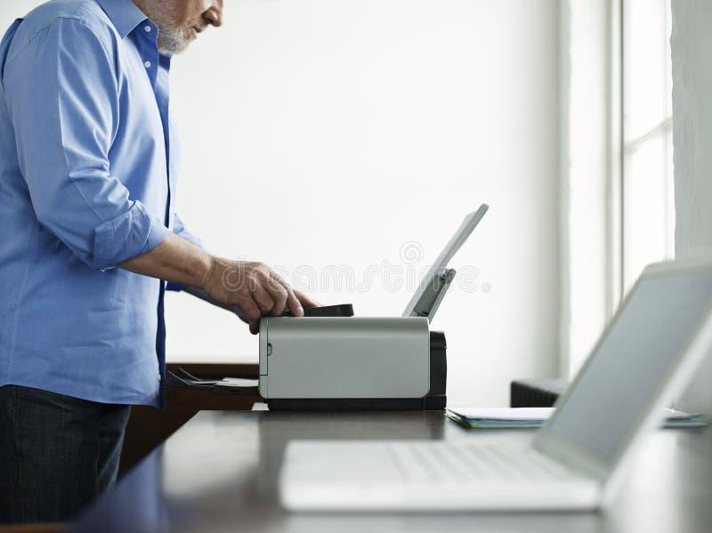 Homem que usa a impressora At Study Table na casa foto de stock